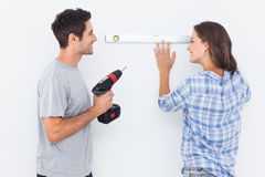 Cheerful man and his wife doing home improvements together. Cheerful men and his wife doing home improvements with a drill and a spirit level Stock Photo