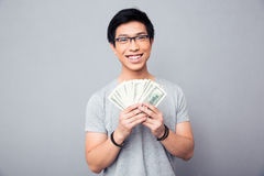 Cheerful man holding bills of US dollars Stock Photos