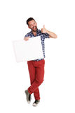 Cheerful man holding blank poster and showing thumbs up royalty free stock photo