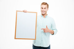 Cheerful man holding blank white board and pointing on it Stock Images