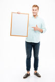 Cheerful man holding blank white board and pointing on it Stock Photos