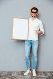 Cheerful man holding blank white board and pointing on it Royalty Free Stock Images