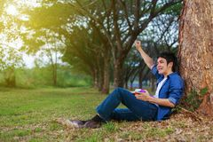Cheerful man  holding a book with arm raised in park. Cheerful man  holding a book with arm raised in the park Royalty Free Stock Image