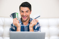 Cheerful man holding credit cards Royalty Free Stock Photos