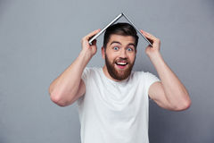 Cheerful man holding laptop over head Royalty Free Stock Images