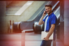 Cheerful man holding laptop and talking on mobile phone Stock Image