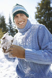 Cheerful Man Holding Snowball Stock Photo