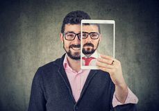 Cheerful man holding a tablet with serious self portrait on screen stock photography