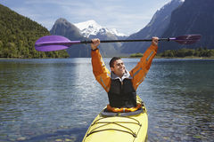 Cheerful Man Holding Up Oar In Mountain Lake Royalty Free Stock Photos