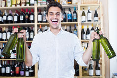 Cheerful man holding wine bottles in winery section. In store Royalty Free Stock Photo