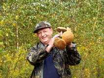 The cheerful man holds in hand mushrooms focus on mushrooms Stock Photos
