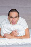 Cheerful man hugging his pillow Stock Images
