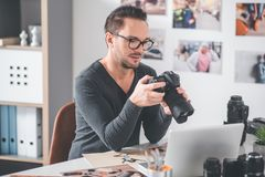 Cheerful man keeping professional camera in hands stock photography