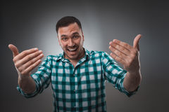 Cheerful man laughing and looking at camera with a big grin. Portrait of a happy young man standing over grey background Royalty Free Stock Image