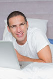 Cheerful man lying on bed using his laptop Royalty Free Stock Photos