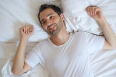 Cheerful man lying in his bed in the morning Stock Images