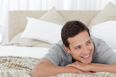 Cheerful man lying in his bedroom Stock Photos