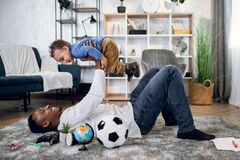 Free Cheerful Man Lying On Carpet And Playing With Baby Boy Royalty Free Stock Photos - 217833428