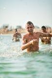 Cheerful man making a splash of water Stock Photo