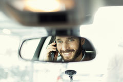 Cheerful man on mobile phone in the car. Reflection in the mirror Royalty Free Stock Photo