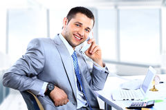 Cheerful man in office answering Royalty Free Stock Images