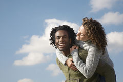 Cheerful Man Piggybacking Woman Royalty Free Stock Photos