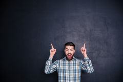 Cheerful man pointing fingers up at copyspace Stock Photos