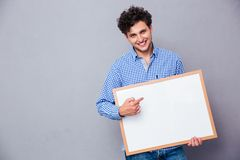 Cheerful man poiting finger on blank board Royalty Free Stock Images