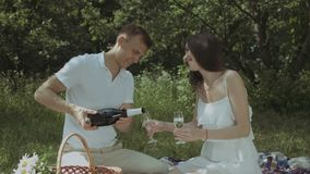 Couple pouring champagne into glasses on picnic. Cheerful man pouring champagne into wineglasses while couple in love enjoying romantic date on picnic in summer stock video footage