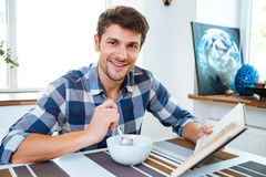 Cheerful man reading book and having breakfast at the table Royalty Free Stock Photography