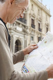 Cheerful Man Reading Map On Street Stock Photos