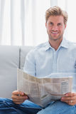 Cheerful man reading a newspaper on a couch Stock Photos