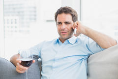 Cheerful man relaxing on sofa with glass of red wine talking on phone Royalty Free Stock Photos