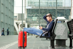 Cheerful man relaxing at train station using mobile phone Royalty Free Stock Photo