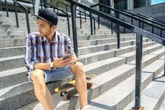 Cheerful man resting on stairs with skate. Young male skater is using smartphone and looking aside pensively. He is sitting on steps near his skateboard Stock Images