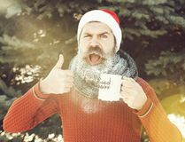 Cheerful man in santa claus hat, bearded hipster with beard and moustache covered with white frost, gives thumbs up hand stock image