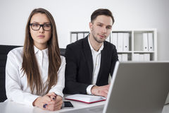 Cheerful man and serious woman in office Royalty Free Stock Photos