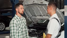 Cheerful man shaking hands with car mechanic at service shop stock video footage