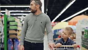 Cheerful man is shopping with his joyful child, they are walking with shopping trolley in supermarket looking around. Cheerful young man is shopping with his stock footage
