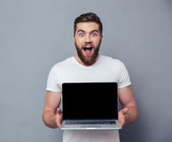 Cheerful man showing blank laptop computer screen. Portrit of a cheerful man showing blank laptop computer screen over gray background Stock Image
