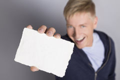 Cheerful man showing blank white card. Fantastic idea: Happy laughing man presenting blank white card with space for text  on grey background, top view Royalty Free Stock Photography