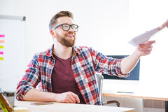 Cheerful man siting on workplace and receiving documents Royalty Free Stock Photo