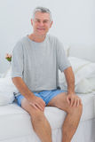 Cheerful man sitting in bed Stock Image