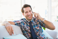 Cheerful man sitting on the couch making a phone call Stock Photo