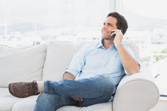 Cheerful man sitting on the couch making a phone call Royalty Free Stock Photos
