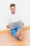 Cheerful man sitting on the floor using laptop Royalty Free Stock Images
