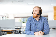 Cheerful man sitting and using headset in office. Cheerful bearded young man sitting and using headset in office Royalty Free Stock Photo