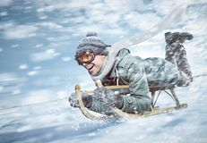 Cheerful man sledding down a snowy slope in full speed. Young man wearing a winter jacket, hat and scarf is lying on a sled while going downhill fast. Snow royalty free stock photos