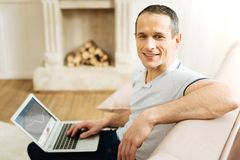 Attractive positive man sitting with his laptop and smiling thoughtfully. Cheerful man. Smart handsome attractive young man looking happy while sitting Stock Photo