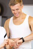 Cheerful man with a smart sport watch at fitness gym Royalty Free Stock Image